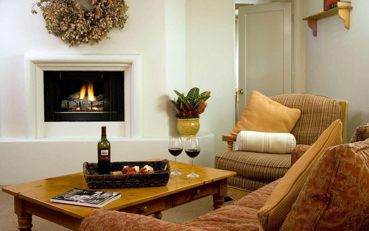 Living room seating area with fireplace and table with wine