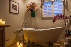Claw foot tub surrounded by candles and flowers