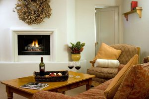 Living room with couch, chair, fireplace, and a table with wine