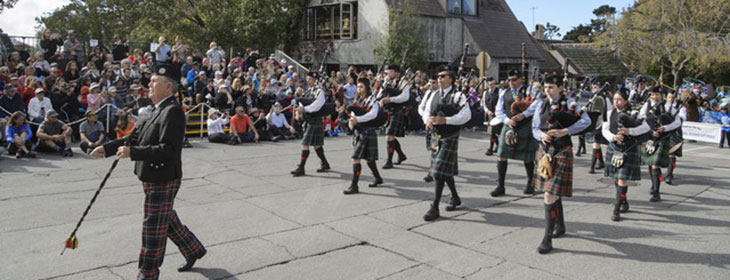 People in kilts playing bagpipes at the 100 Year Parade