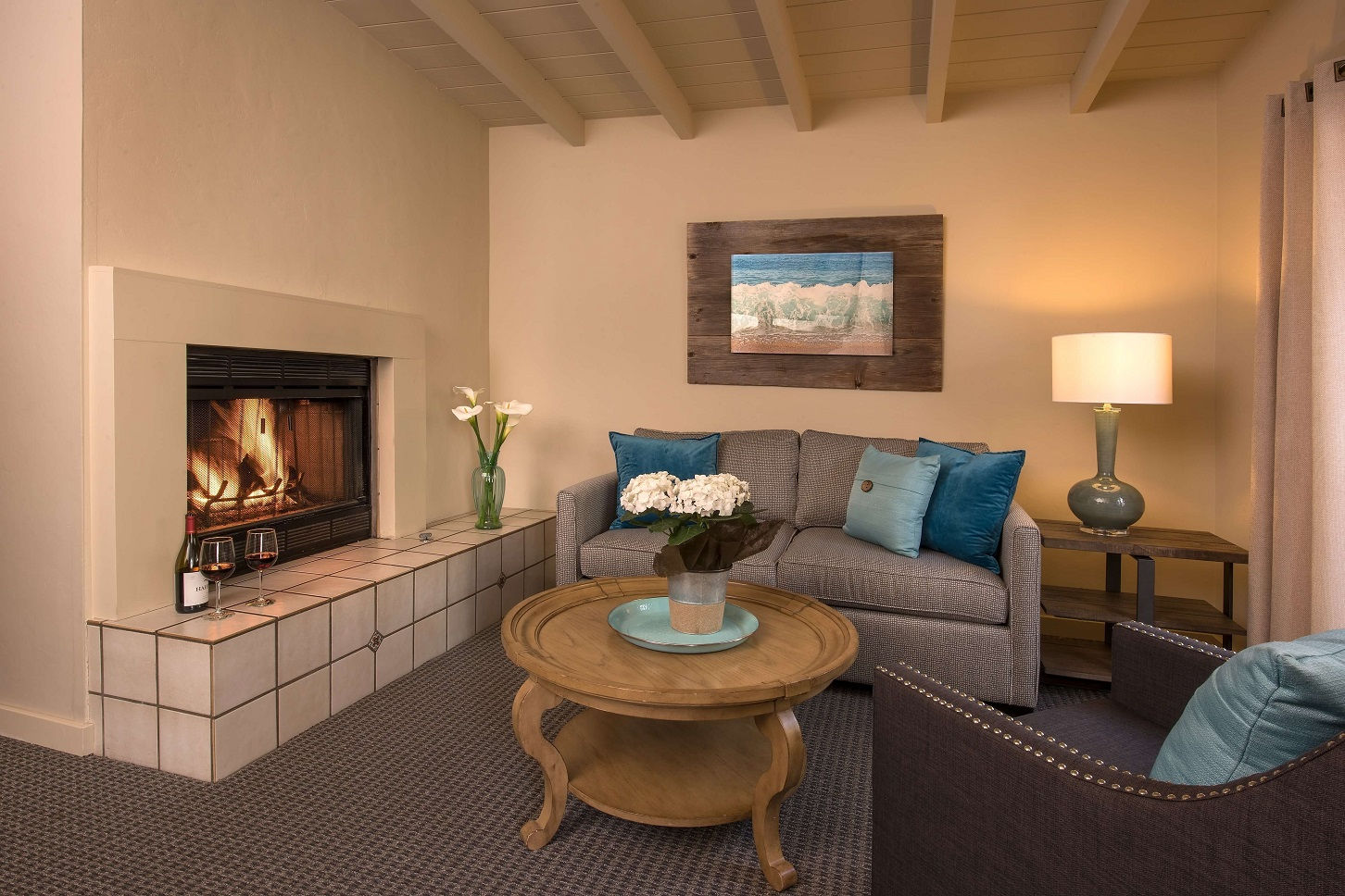 Room seating area with couch, chair, and fireplace