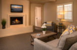 sitting room in  two bedroom suite with fireplace and gray decor