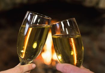 Toasting champagne in front of a fireplace