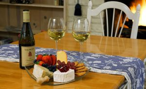 Fruit and cheese plate with wine on a table