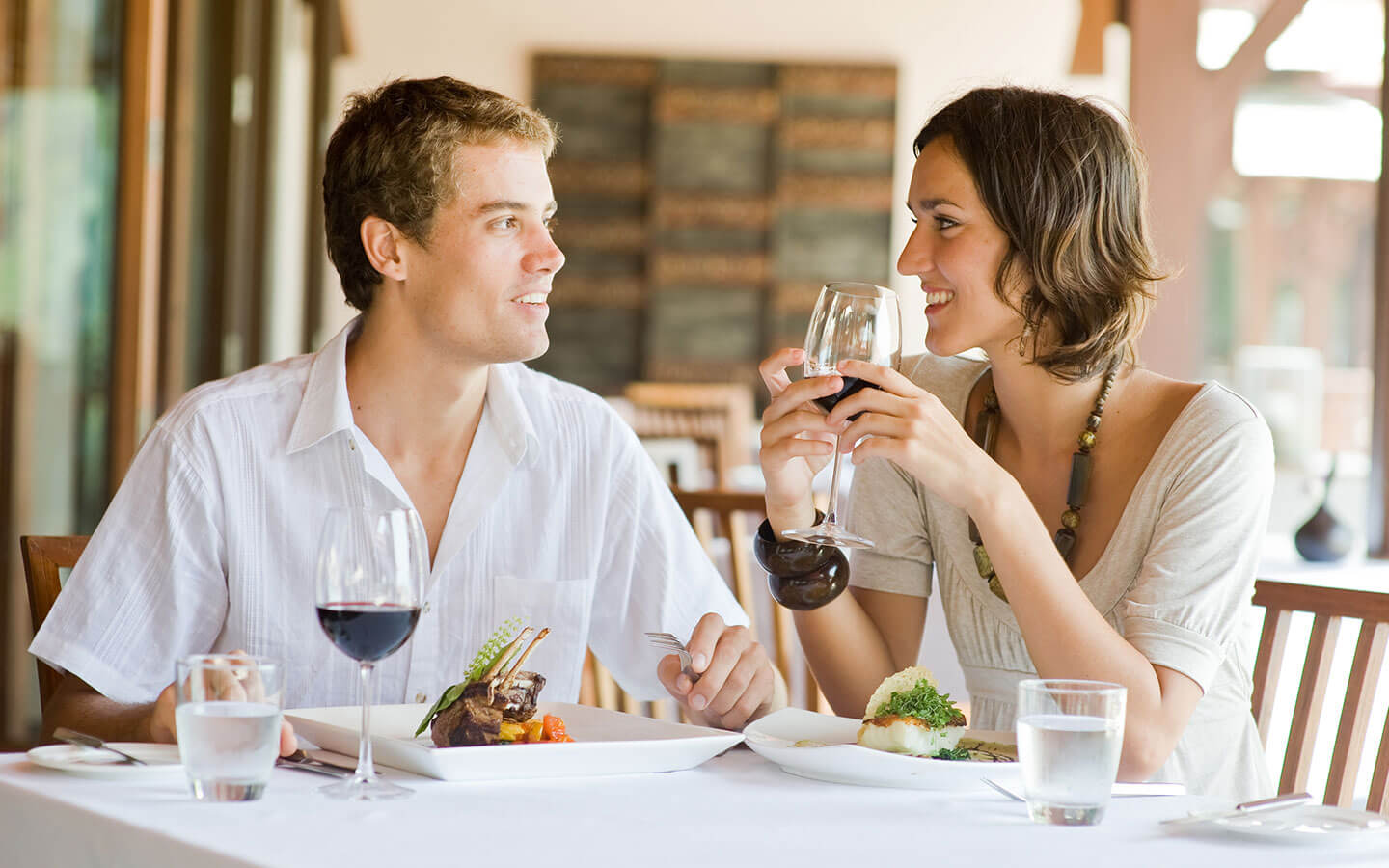 Happy young couple drinking wine and eating at a nice restaurant