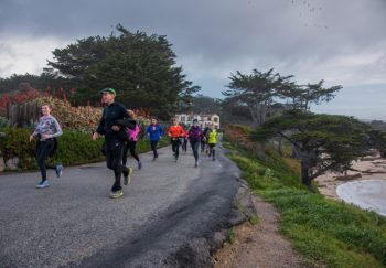 Group of people running with Jeff Galloway on a road near the ocean