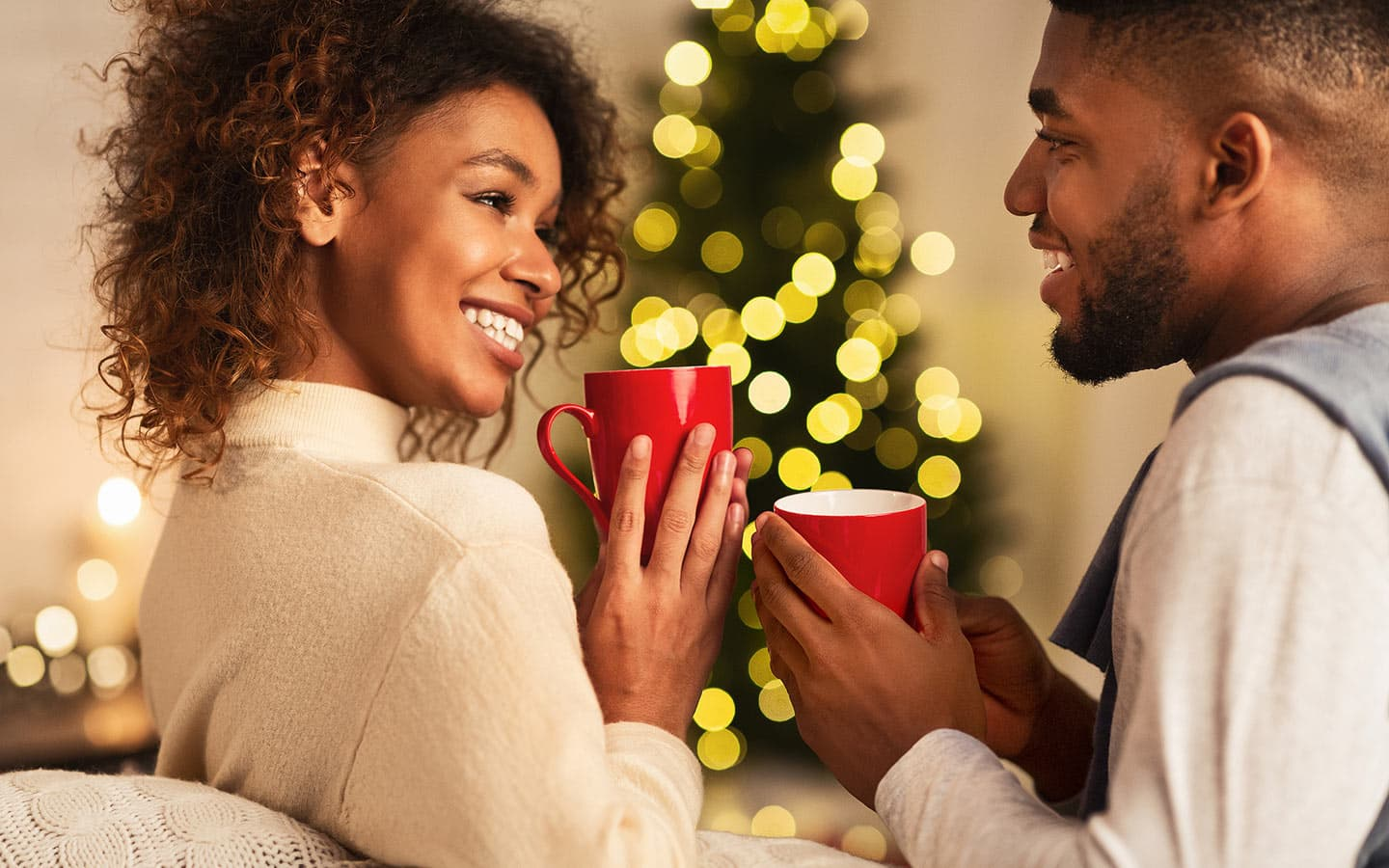 Couple drinking hot cocoa by a Christmas Tree